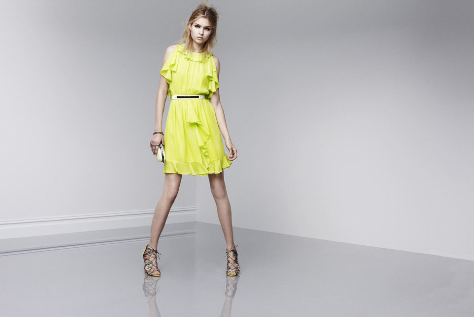 "One trick to ""dressing rich"" is to wear a ""statement"" dress, according to fashion expert Anna Johnson. Here is a bright lemon yellow ruffled dress with statement shoes from Prabal Gurung's new designer collection at Target, coming out Feb. 10. <strong></strong>"