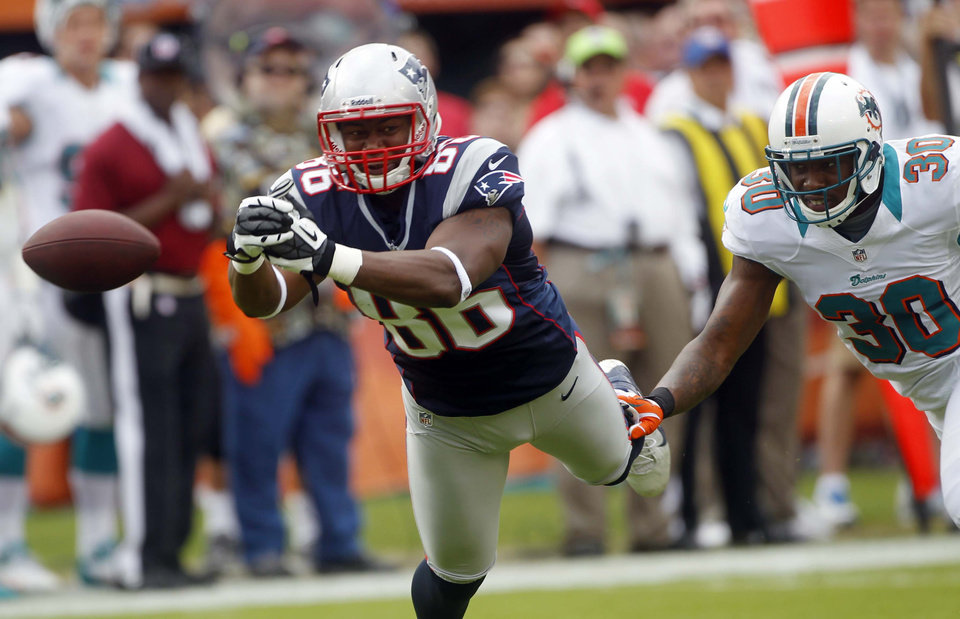 Photo - New England Patriots tight end Daniel Fells (86) cannot hold on to a pass as Miami Dolphins strong safety Chris Clemons (30) defends during the first half of an NFL football game on Sunday, Dec. 2, 2012, in Miami. (AP Photo/John Bazemore)