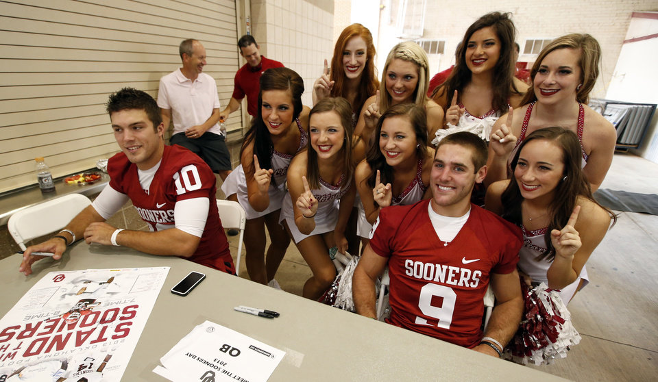Photo - Sooner cheer squad members pose with quarterbacks Blake Bell,left, and Trevor Knight during fan appreciation day for the University of Oklahoma Sooner (OU) football team at Gaylord Family-Oklahoma Memorial Stadium in Norman, Okla., on Saturday, Aug. 3, 2013. Photo by Steve Sisney, The Oklahoman