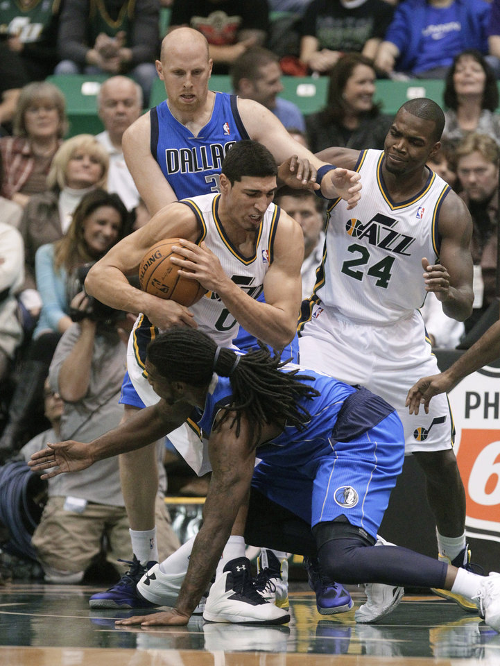 Photo - Utah Jazz center Enes Kanter (0) pulls down a rebound as Mavericks small forward Jae Crowder falls to his knees while Mavericks center Chris Kaman (35) and Jazz forward Paul Millsap (24) look on in the second quarter during an NBA basketball game Monday, Jan. 7, 2013, in Salt Lake City. (AP Photo/Rick Bowmer)