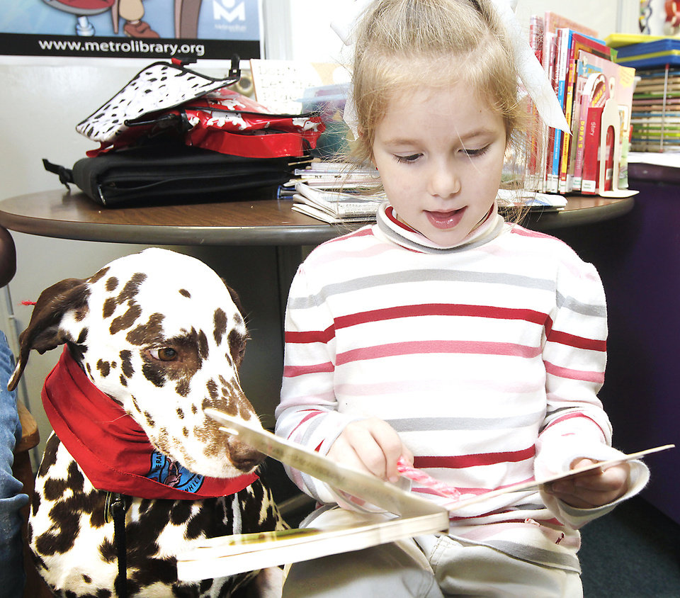 Paige Fowler, 6, reads to D'Leo, a Dalmatian therapy dog, at the Nicoma Park Library. D'Leo visits the library Thursday as part of the Children Reading to Dogs program. PHOTO BY STEVE GOOCH, THE OKLAHOMAN