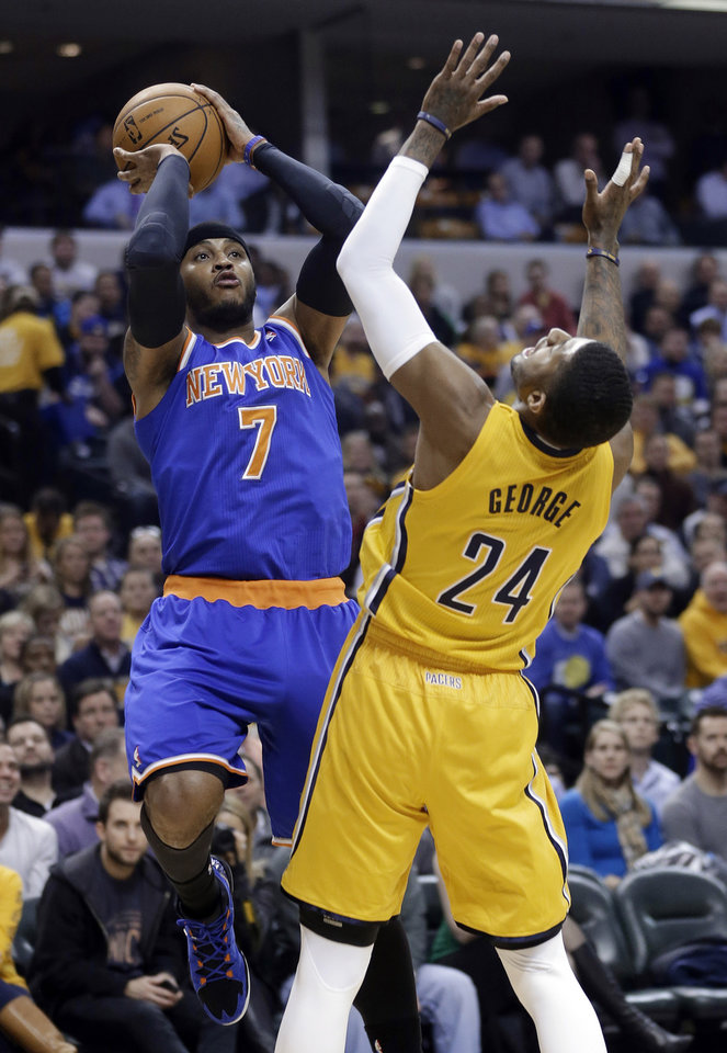 Photo - New York Knicks forward Carmelo Anthony, left, shoots over Indiana Pacers forward Paul George during the first half of an NBA basketball game in Indianapolis, Thursday, Jan. 16, 2014. (AP Photo/Michael Conroy)