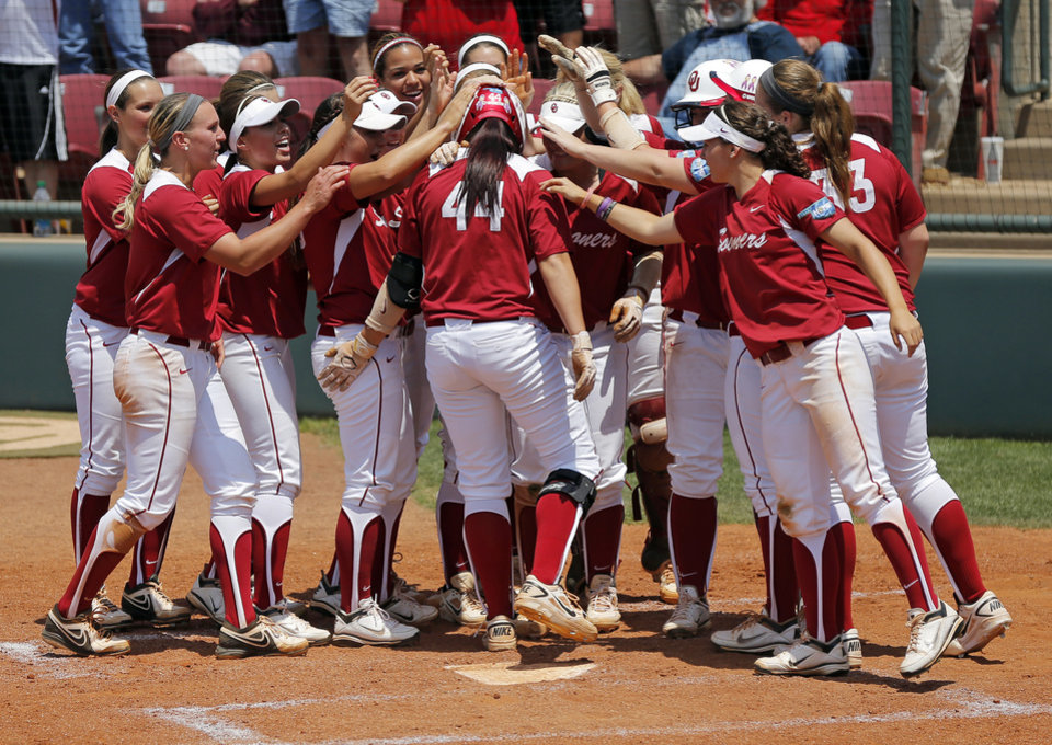 Photo - OU's Lauren Chamberlain (44) is greeted at home plate after hitting a 2-run home run in the fourth inning during the final game of the Norman Regional in 2014 NCAA softball championship between Oklahoma and Texas A&M in Norman, Okla., Sunday, May 18, 2014. OU won 11-6. Photo by Nate Billings, The Oklahoman