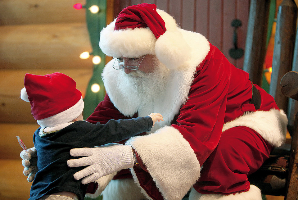Photo - Zachary Anderson, 1, is greeted by Santa at Bass Pro Shops in Oklahoma City. Photo by SARAH PHIPPS, THE OKLAHOMAN