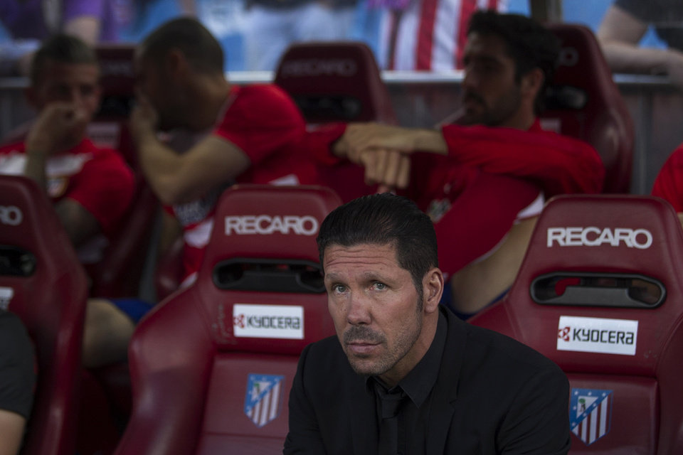 Photo - Atletico's coach Diego Simeone sits before a Spanish La Liga soccer match between Atletico de Madrid and Elche at the Vicente Calderon stadium in Madrid, Spain, Friday, April 18, 2014. (AP Photo/Gabriel Pecot)