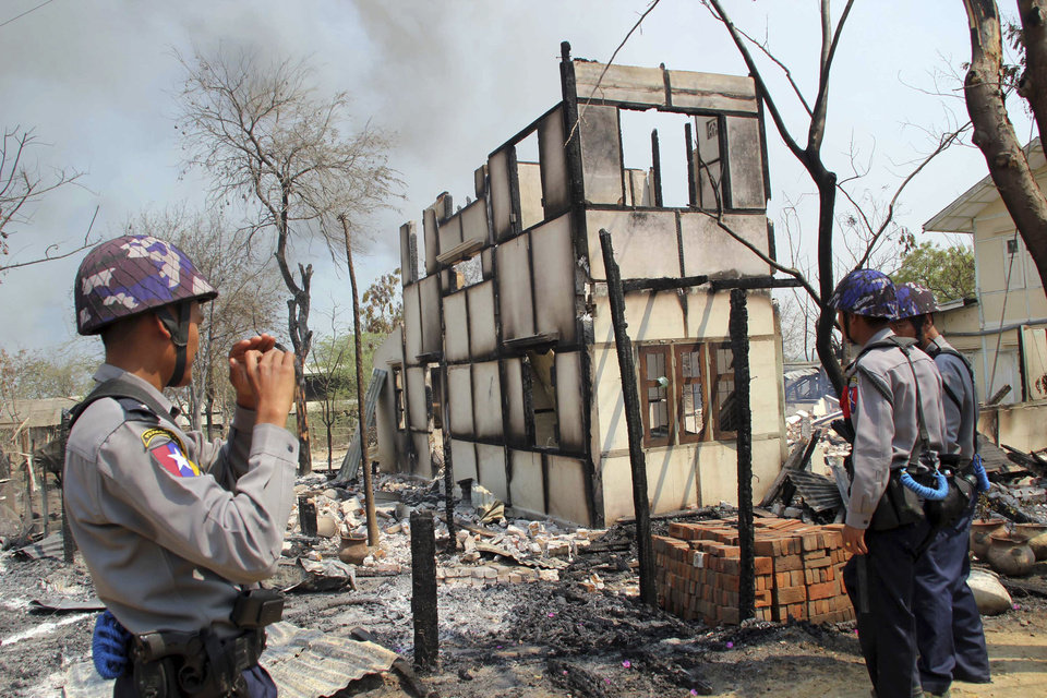 In this Thursday, March. 21, 2013, police officers stand near burnt building in Meikhtila, where Ethnic unrest between Buddhists and Muslims continues, in Mandalay division, about 550 kilometers (340 miles) north of Yangon, Myanmar, Friday, March.22, 2013. Burning fires from two days of Buddhist-Muslim violence that killed at least 20 people smoldered across a central Myanmar town Friday as residents cowered indoors amid growing fears the country's latest bout of sectarian bloodshed could spread. The government's struggle to contain the unrest in Meikhtila is proving another major challenge President Thein Sein's reformist administration as it attempts to chart a path to democracy after nearly half a century of military rule that once crushed all dissent. (AP Photo)