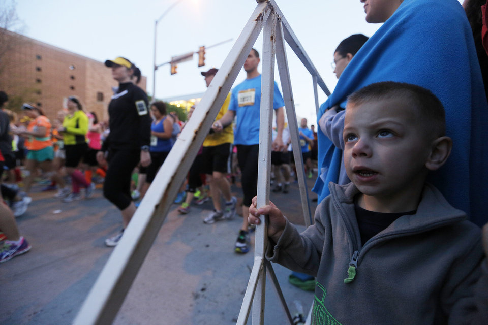 Jaxon Klutinis, 3, watches runners at the starting line during the Oklahoma City Memorial Marathon in Oklahoma City, Sunday, April 28, 2013.  Photo by Garett Fisbeck, For The Oklahoman