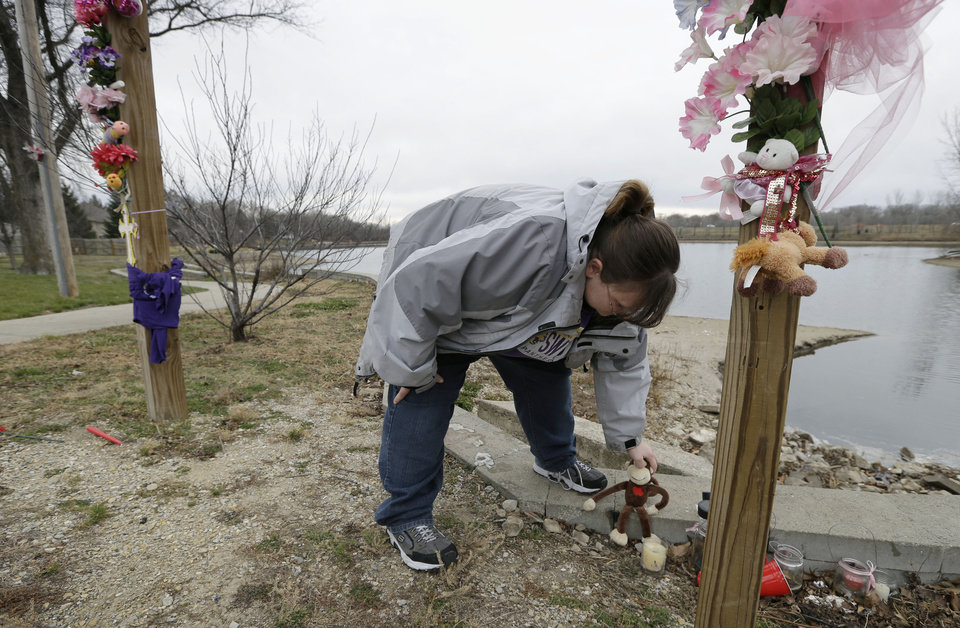 Tasha Gant, of Waterloo, Iowa, places a stuffed monkey at a memorial site at Meyers Lake Thursday, Dec. 6, 2012, in Evansdale, Iowa, where cousins Lyric Cook, 10, and Elizabeth Collins, 8, disappeared in July while riding their bikes. Family members are waiting to hear whether the two bodies discovered by hunters on Wednesday are the two missing cousins. (AP Photo/Charlie Neibergall)