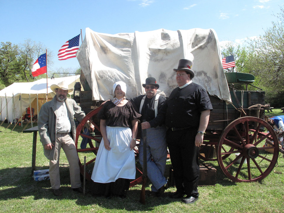 Photo - Chip Hancock and Kathy and Phil Rattan pose for a picture with the Rev. John Malget near a covered wagon during the 124th anniversary celebration of First Christian Church of Oklahoma City (Disciples of Christ) on April 21 at 3700 N Walker. Photo by Carla Hinton, The Oklahoman