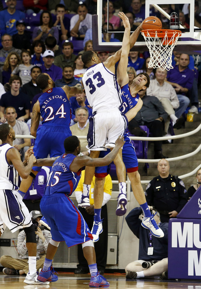 Photo - TCU forward Garlon Green (33) dunks as Kansas guards Travis Releford (24) and Elijah Johnson (15) and center Jeff Withey (5) defend during the second half of an NCAA college basketball game, Wednesday, Feb. 6, 2013, in Fort Worth, Texas. TCU won 62-55. (AP Photo/Sharon Ellman)