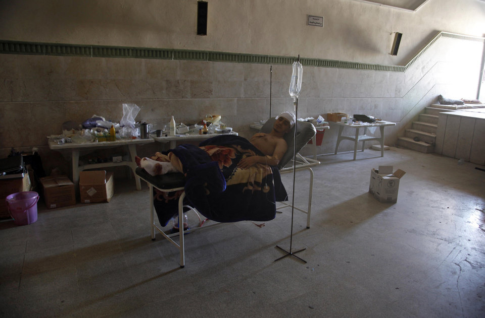 Photo -   Palestinian refugee, Mohammed, first name not given, rests in a field hospital after he was found in an open area with three gunshot wounds among the bodies of nine other people in the town of Anadan on the outskirts of Aleppo, Syria, Monday, Aug. 6, 2012. (AP Photo)