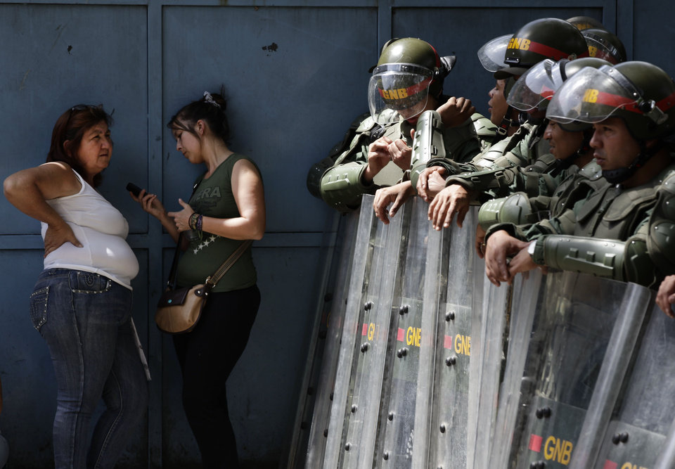 Photo -   Inmates' relatives stand outside La Planta prison by National Guard soldiers in Caracas, Venezuela, Saturday, April 28, 2012. Hundreds of inmate's relatives were not allowed to enter for normal visiting hours because they were canceled after authorities foiled plans for a prison break on Friday. Venezuelan authorities say they discovered a tunnel that inmates had dug leading to a sewer. (AP Photo/Ariana Cubillos)