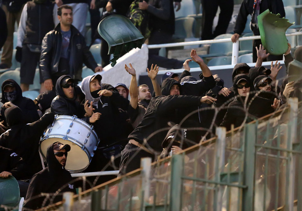 Photo - PAOK fans throw seats at Panathinaikos supporters shortly before the start of the Greek championship play-off match between their teams at Apostolos Nikolaidis stadium in Athens, Sunday, May 4, 2014. (AP Photo/InTime Sports)  GREECE OUT