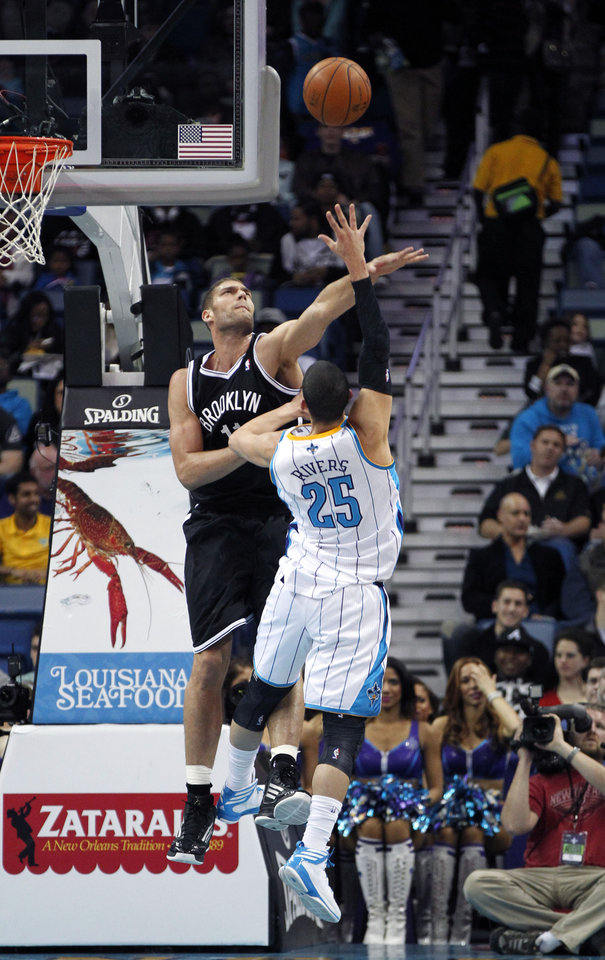 Brooklyn Nets center Brook Lopez (11) tries to block a shot by New Orleans Hornets guard Austin Rivers (25) in the first half of an NBA basketball game in New Orleans, Tuesday, Feb. 26, 2013. (AP Photo/Gerald Herbert)