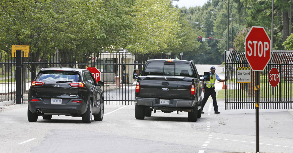 Photo - Security guards open a gate for motorist at the visitor entrance to Fort Lee, Va., Monday, Aug. 25, 2014.  A female soldier with a gun inside a key building at a Virginia Army base turned the weapon on herself, causing an injury, but didn't wound any others as the heavily trafficked base temporarily went on lockdown Monday morning.  (AP Photo/Steve Helber)