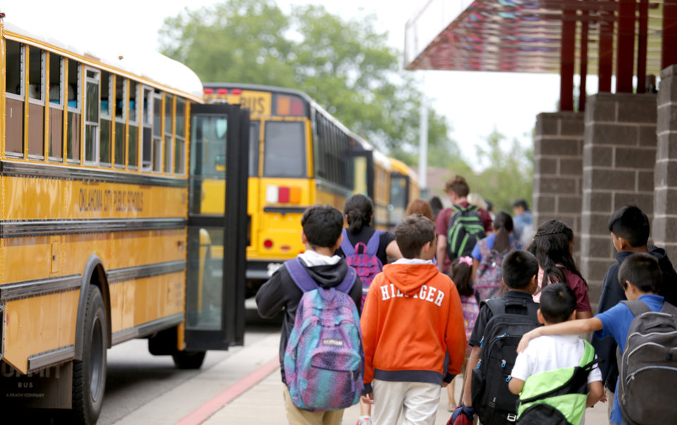 Photo -  Students board buses at Cesar Chavez Elementary school in Oklahoma City in May. [Photo by Sarah Phipps, The Oklahoman Archives]