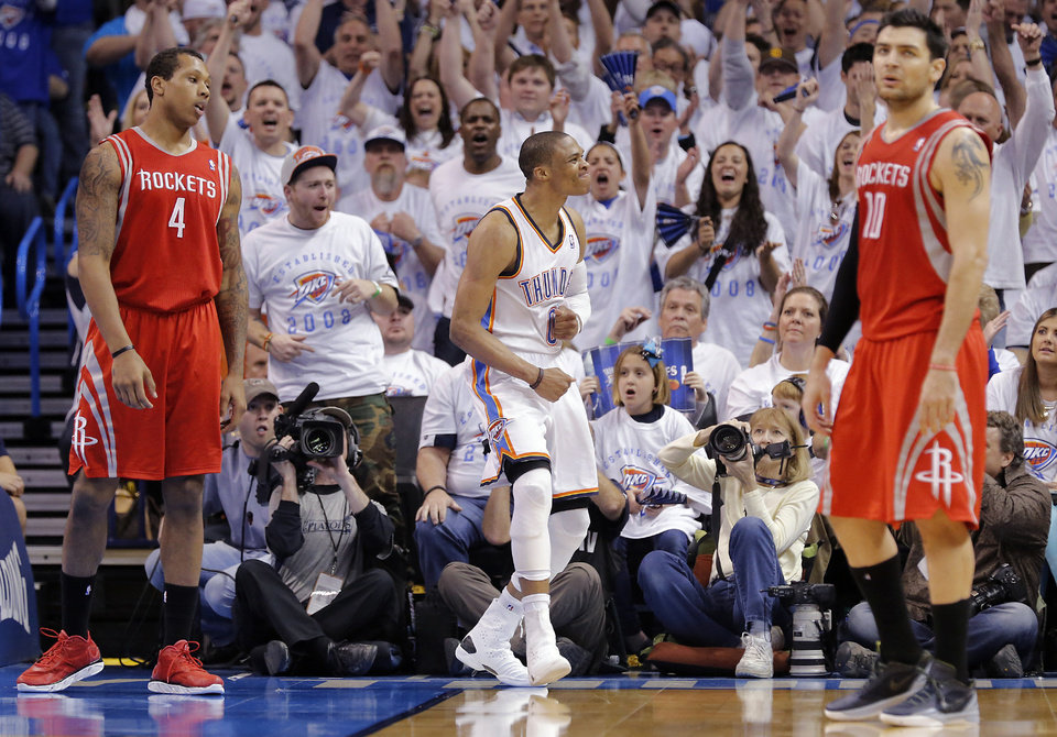 Photo - Oklahoma City's Russell Westbrook (0) reacts after making a shot in front of Houston's Greg Smith (4) and Carlos Delfino (10) during Game 2 in the first round of the NBA playoffs between the Oklahoma City Thunder and the Houston Rockets at Chesapeake Energy Arena in Oklahoma City, Wednesday, April 24, 2013. Photo by Chris Landsberger, The Oklahoman