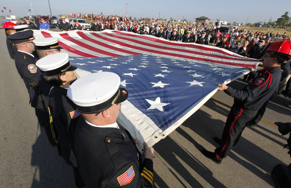 First responders hold the National September 11 flag during a ceremony in Joplin, Mo., Sunday, Sept. 11, 2011 marking the end of the 50 state restoration tour. The final stitches are being placed in Joplin and then the flag will go to the National 9/11 Memorial Museum. (AP Photo/Paul Sancya)