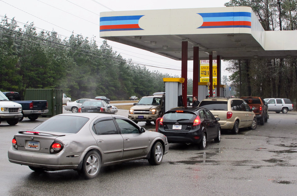 Photo - Cars line up for gas at a store on U.S. 501 west of Georgetown, S.C. on Thursday, Feb. 13, 2014 following the worst winter storm to hit the state in a decade. The storm left hundreds of thousands without power in South Carolina. Patrons said the convenience store was the only one with power for miles. (AP Photo/Bruce Smith)