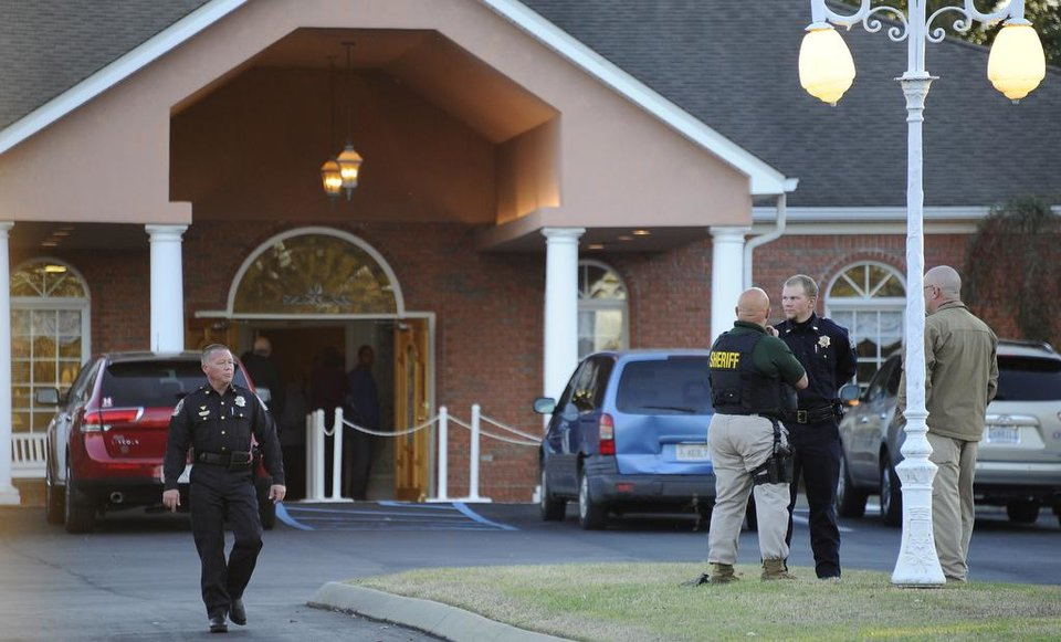 Photo - Law enforcement personnel wait outside the funeral home as people pay their respects to Charles Albert