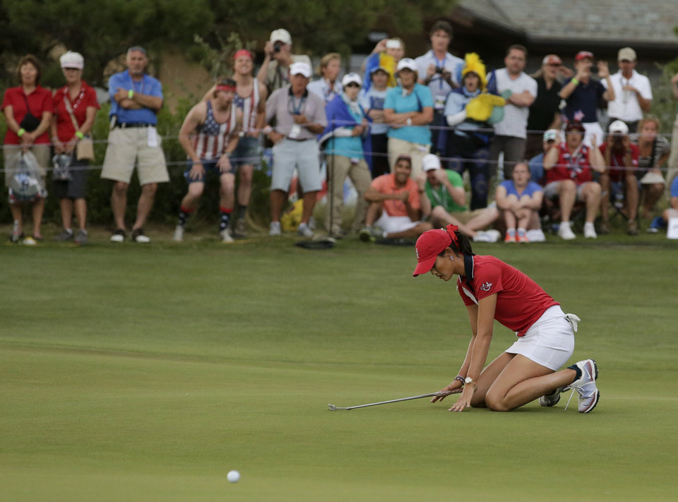 Photo - United States' Michelle Wie reacts after reacts after missing a birdie putt on the 18th hole during her singles match at the Solheim Cup golf tournament, Sunday, Aug. 18, 2013, in Parker, Colo. (AP Photo/Chris Carlson)
