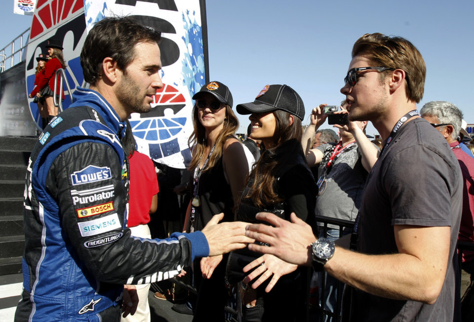 "Jimmie Johnson, left, shakes hands and talks with actors Josh Henderson, right, Jordana Brewster, second from right, and Julie Gonzalo, third from left, of the television show ""Dallas,"" before a NASCAR Sprint Cup Series auto race, Sunday, Nov. 4, 2012, in Fort Worth, Texas. (AP Photo/Tim Sharp)"