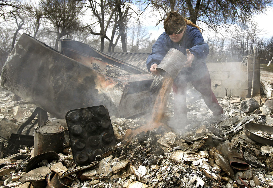 Carrie Wertz dumps sand on a smoldering section that remains from her home that was destroyed by wildfires on Friday, April 10, 2009, in Choctaw, Okla.  Photo by Chris Landsberger, The Oklahoman