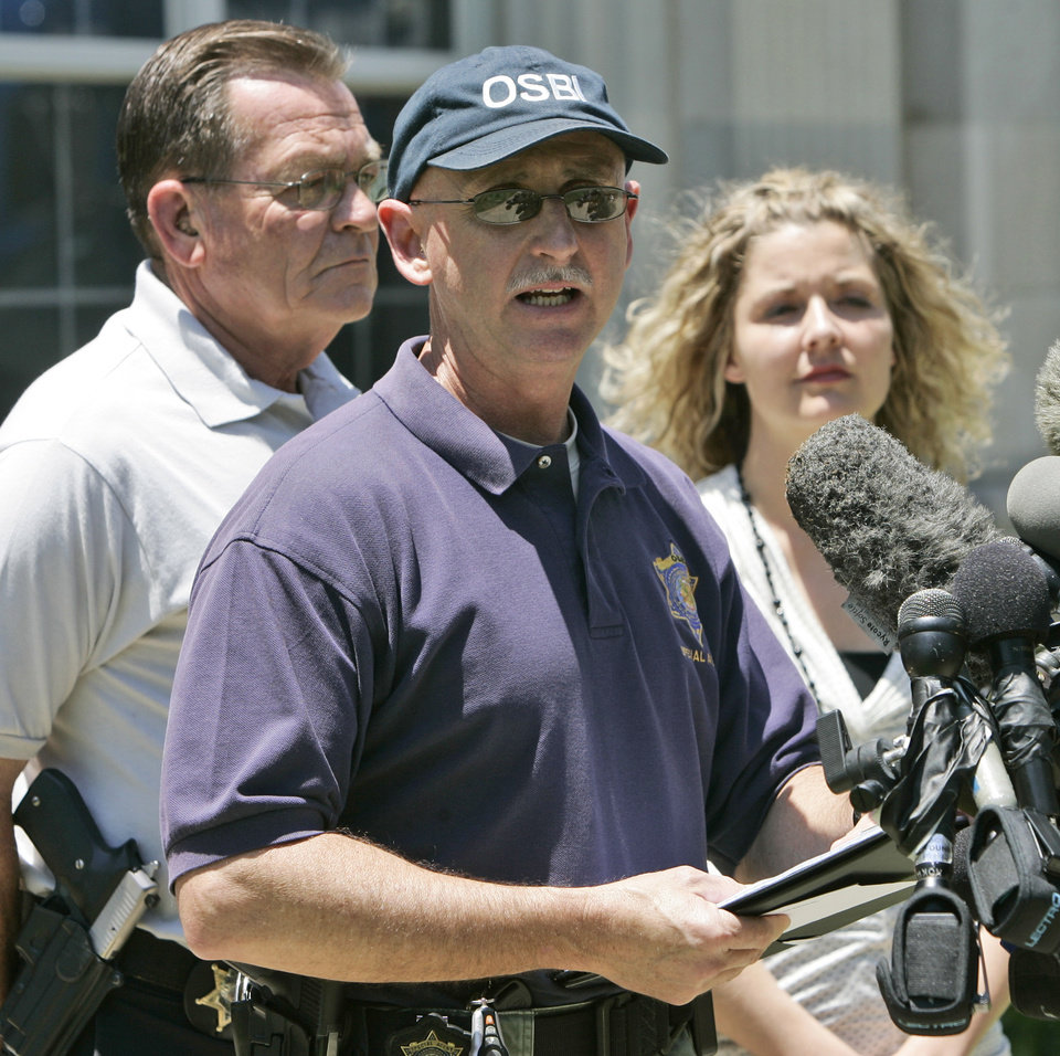 Photo - Special Agent Ben Rosser, center, of the Oklahoma State Bureau of Investigation, speaks at a news conference in front of the Okfuskee County Courthouse in Okemah, Okla., Wednesday, June 11, 2008, concerning the murders of Skyla Whitaker and Taylor Paschal-Placker, in nearby Weleetka, Okla., Sunday night. At left is Okfuskee County Sheriff Jack Choate. At right is Maxey Reilly, assistant district attorney. (AP Photo)