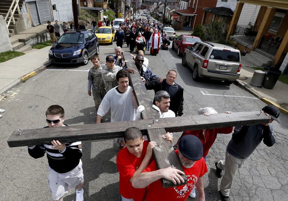 Photo - Volunteers carry a wooden cross walk in a procession through the streets of Etna, Pa., a Pittsburgh suburb, on Good Friday, Friday, April 18, 2014, as part of their annual