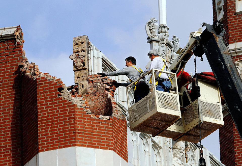 Photo - EARTHQUAKE DAMAGE: An eathquake late Saturday night caused extensive damage to the towers (turrets) atop Benedictine Hall, the most prominent structure on the campus of St. Gregory's University in Shawnee.  Crews from the university's maintenance department used a large crane on  Sunday afternoon, Nov. 6, 2011, to remove loosened bricks and  place a large top over the southwest tower's opening.  Photo by Jim Beckel, The Oklahoman  ORG XMIT: KOD