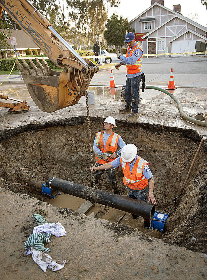 Photo - City of Fullerton maintenance workers Ernie Vejar, left, Eric Becerra and Andrew Grajeda, above, lower in a new section of pipe Saturday, March 29, 2014,   as they work on repairing a main water line in Fullerton, Calif. More than 100 aftershocks have rattled Orange County south of Los Angeles where a magnitude-5.1 earthquake struck Friday.  Despite the relatively minor damage, no injuries have been reported. (AP Photo/The Orange County Register, Ken Steinhardt)   MAGS OUT; LOS ANGELES TIMES OUT