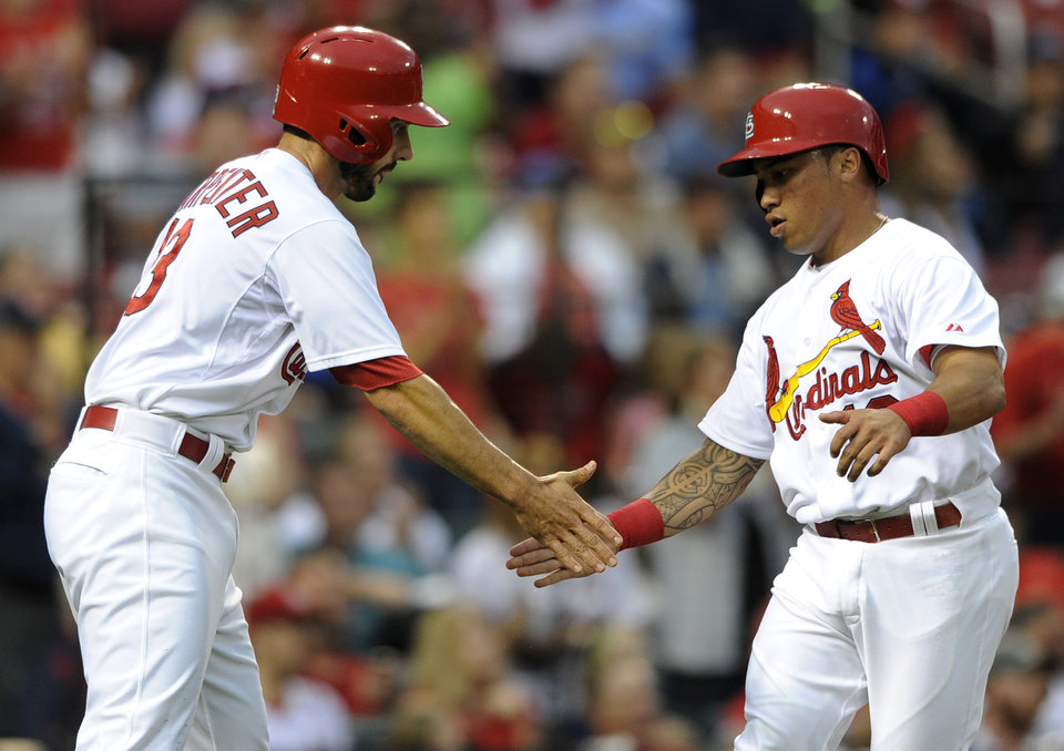 Photo - St. Louis Cardinals' Matt Carpenter, left, and Kolten Wong celebrate after scoring on a two-run double by teammate Jhonny Peralta against the Boston Red Sox in the first inning in a baseball game, Thursday, Aug. 7, 2014, at Busch Stadium in St. Louis. (AP Photo/Bill Boyce)