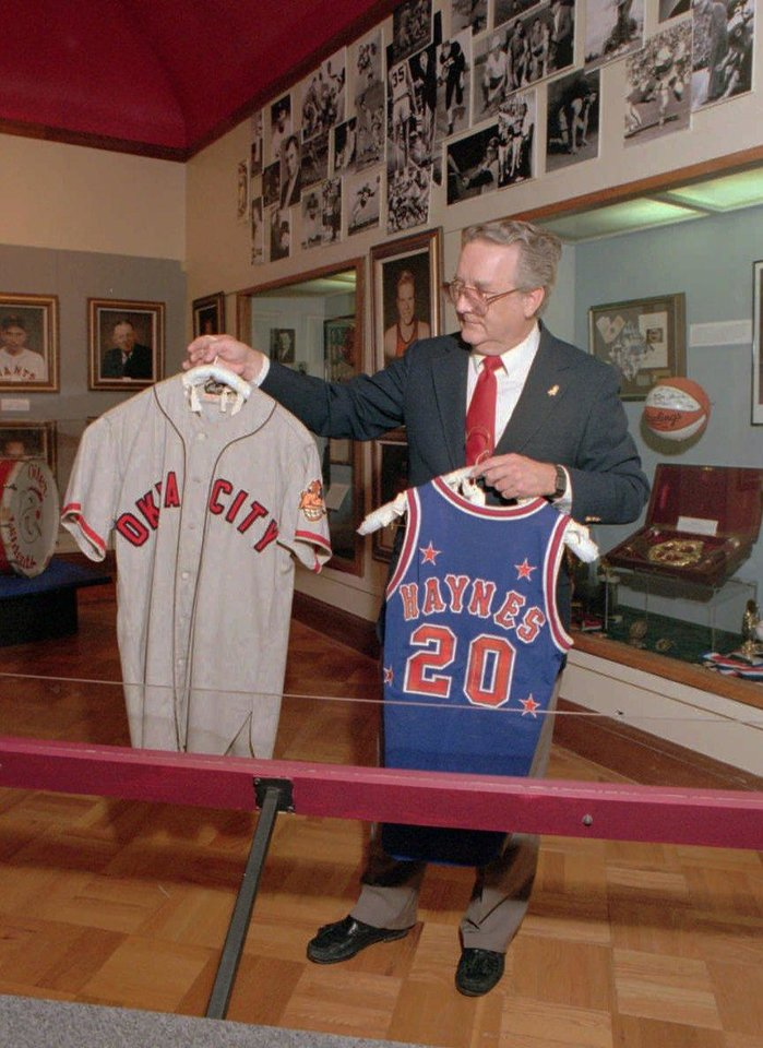 Photo - Lynne Draper holds up part of a 1948 Oklahoma City Indians baseball uniform in his right hand a the jersey top of basketball great Marques Haynes in his left hand as he displays some of the memorabilia to be found at the Oklahoma Sports Hall of Fame at NE 22 and Lincoln in OKC. Draper was inducted into the Oklahoma Sports Hall of Fame on March 20, 2012. (Staff Photo by Roger Klock)