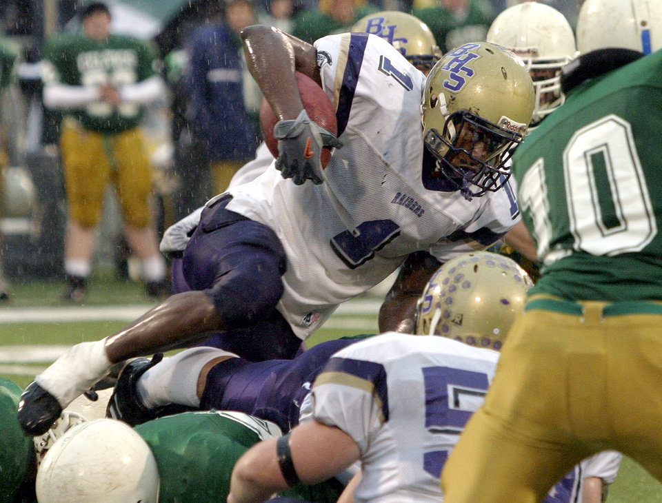 Photo - FILE - In this Nov. 27, 2004 file photo, Bloomington High School running back Adrian Arrington tries to clear a pile of Providence Catholic defenders during the Class 6A championship football game in Champaign, Ill. Arrington, who later went on to play at Eastern Illinois in Charleston, is the lead plaintiff in a class-action head injury lawsuit working its way through federal court in Chicago. The NCAA and the plaintiffs announced a settlement on Tuesday, July 29, 2014. (AP Photo/ Stephen Haas, File)