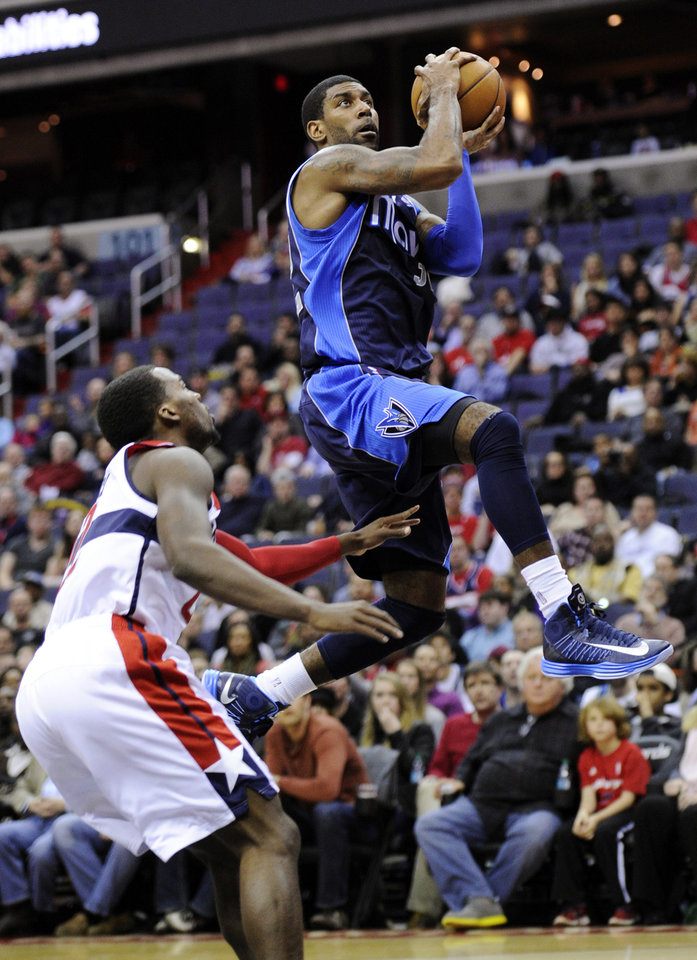 Dallas Mavericks guard O.J. Mayo, right, goes to the basket against Washington Wizards guard Shelvin Mack, left, during the first half of an NBA basketball game, Tuesday, Jan. 1, 2013, in Washington. (AP Photo/Nick Wass)