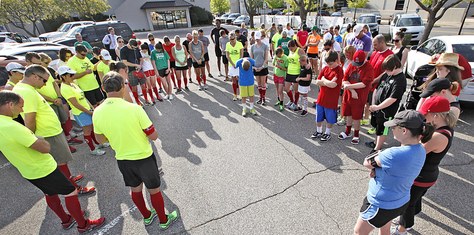 Edmond runners pray before running a three-mile informal marathon in honor of the Boston Marathon bombing tragedy. PHOTO BY DAVID MCDANIEL, THE OKLAHOMAN. <strong>David McDaniel - The Oklahoman</strong>