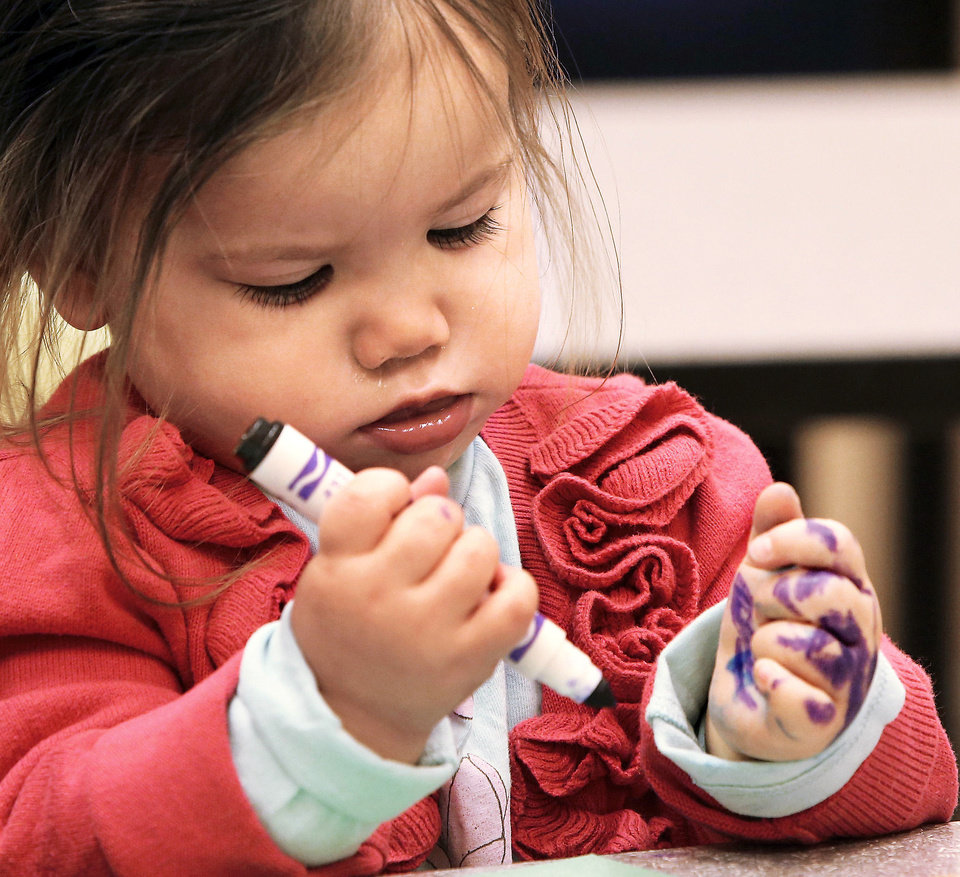 Sophie Alexander is more interested in coloring her hand while her older sister, Ella, 4, attends a session of Tiny Tuesdays at the Oklahoma City Museum of Art.    Photo by Jim Beckel, The Oklahoman <strong>Jim Beckel - THE OKLAHOMAN</strong>