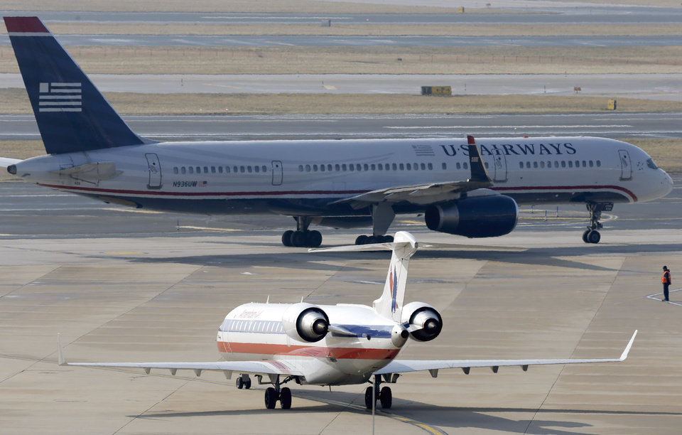 Photo - An American Airlines jet taxis near a US Airways jet at the Philadelphia International Airport, Thursday, Feb. 14, 2013, in Philadelphia. The merger of US Airways and American Airlines has given birth to a mega airline with more passengers than any other in the world.  (AP Photo/Matt Rourke)