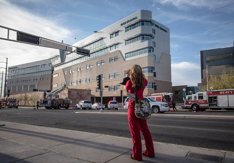 Photo - A hospital employee takes a picture  of a helicopter's tail hanging over the edge of the UNM Hospital  Wednesday afternoon April 9, 2013 in Albuquerque, N.M. The helicopter crashed as it  took off from the roof of the building.  (AP Photo/The Albuquerque Journal, Robert E. Rosales)  THE SANTA FE NEW MEXICAN OUT