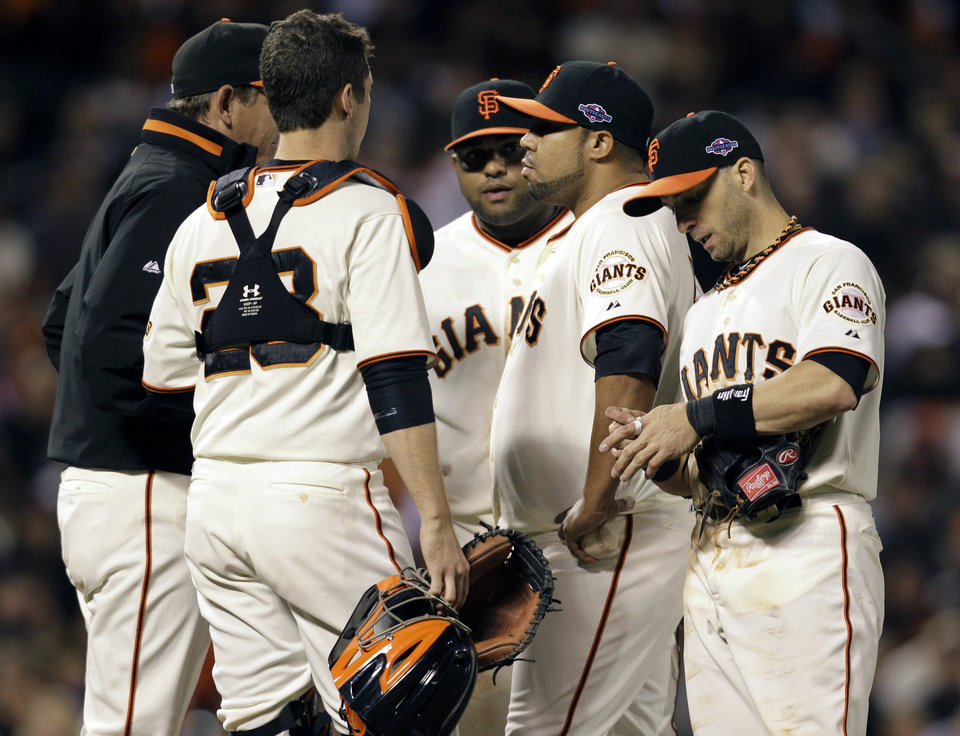 San Francisco Giants pitcher Jose Mijares, second from right, has a conference on the mound after he gave up a two-run double in the eighth inning during Game 2 of the National League division baseball series against the Cincinnati Reds in San Francisco, Sunday, Oct. 7, 2012. (AP Photo/Eric Risberg)