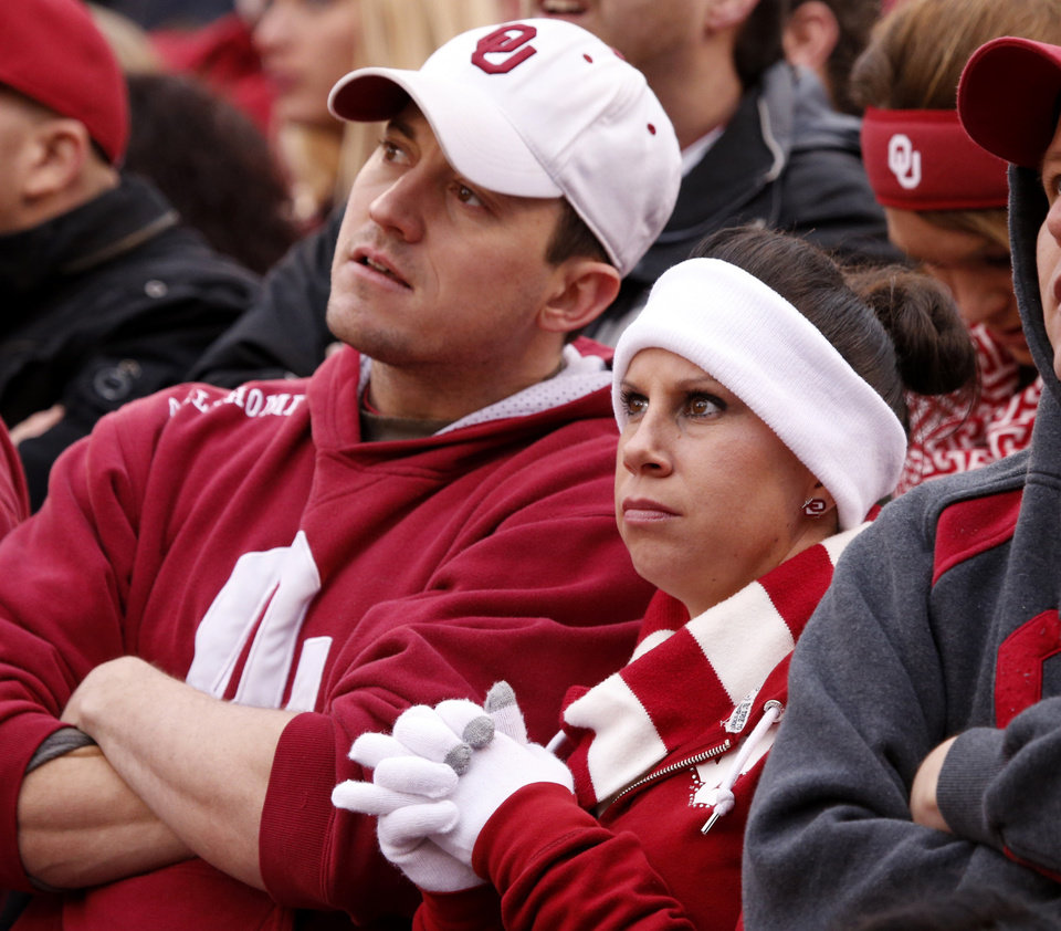 Photo - Nick and felicia Norvell watch the scoreboard during a Bedlam college football game between the University of Oklahoma Sooners (OU) and the Oklahoma State Cowboys (OSU) at Gaylord Family-Oklahoma Memorial Stadium in Norman, Okla., on Saturday, Dec. 6, 2014. Photo by Steve Sisney, The Oklahoman