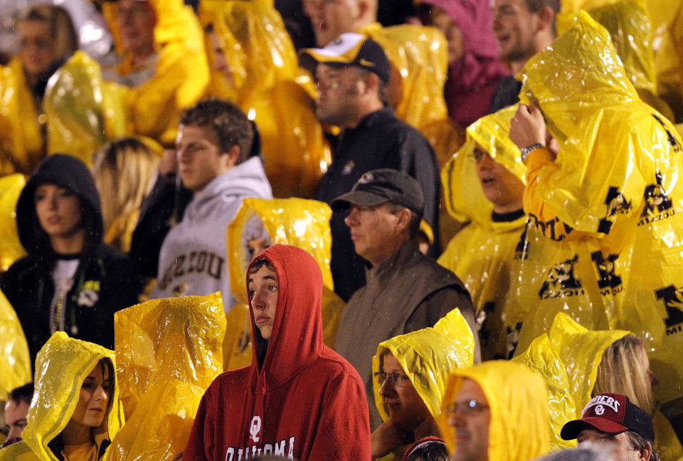 Photo - An Oklahoma fan is surrounded by Missouri Tiger fans while watching the game from the stands during the second half of the college football game between the University of Oklahoma Sooners (OU) and the University of Missouri Tigers (MU) on Saturday, Oct. 23, 2010, in Columbia, Mo. Oklahoma lost the game 36-27. Photo by Chris Landsberger, The Oklahoman