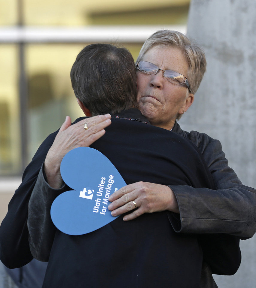 Photo - Plaintiffs Laurie Wood, right, and Kody Partridge, left, hug at the Utah Unites for Marriage