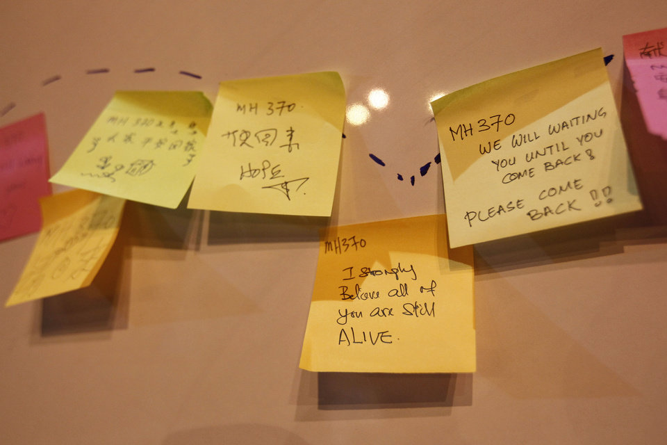 Photo - Notes with messages for passengers aboard the missing Malaysia Airlines Flight MH370 are pasted on a board during a candlelight vigil in Kuala Lumpur, Malaysia, Sunday, April 6, 2014. Searchers hunting for the missing Malaysia Airlines jet were racing to a patch of the southern Indian Ocean on Sunday to determine whether a few brief sounds picked up by underwater equipment came from the plane's black boxes, whose battery-operated beacons are on the verge of dying out. (AP Photo/Lai Seng Sin)
