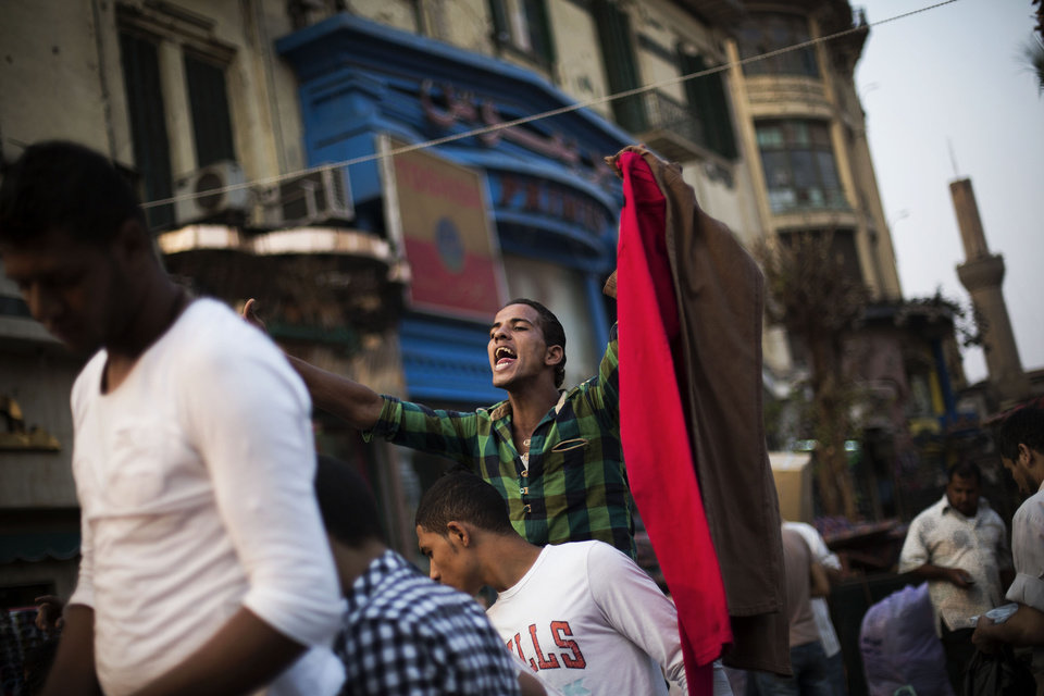 Photo - An Egyptian street vendor shouts the prices of his products in the Ataba market on the eve of Eid al-Adha, or Festival of the Sacrifice, one of the most important celebrations in the Muslim calendar, in Cairo, Egypt, Monday, Oct. 14, 2013. (AP Photo/Manu Brabo)