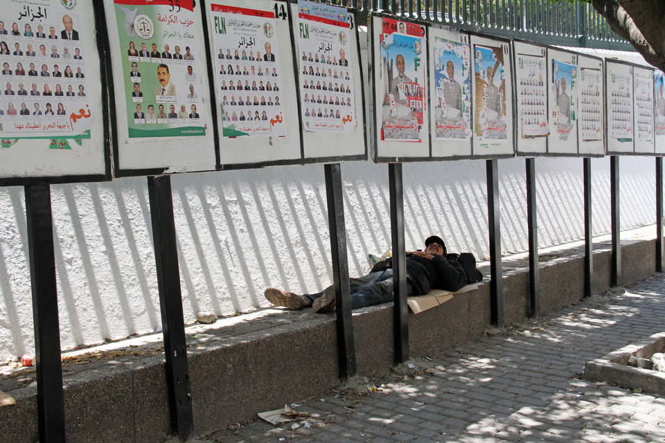 Photo -   An Algerian sleeps in the shade provided by rows of election posters Thursday May 10, 2012, in the capital Algiers on the day of parliamentary elections. Parliamentary elections in Algeria are being billed as the fairest in 20 years, but as polls opened Thursday disgruntled Algerians appeared to be showing little interest and even outright scorn for the vote. (AP Photo/Paul Schemm).