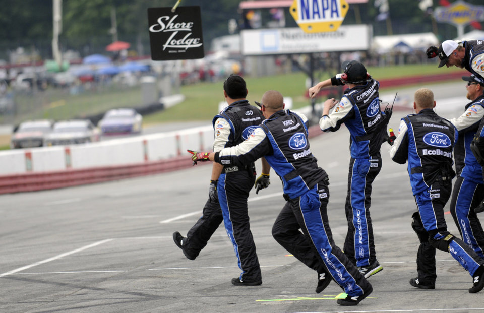 Photo - Chris Buescher's Roush Fenway crew celebrates after he crossed the finish line to win the NASCAR Nationwide Series Nationwide Children's Hospital 200 auto race at Mid-Ohio Sports Car Course, Saturday, Aug. 16, 2014, in Lexington, Ohio. (AP Photo/Tom E. Puskar)