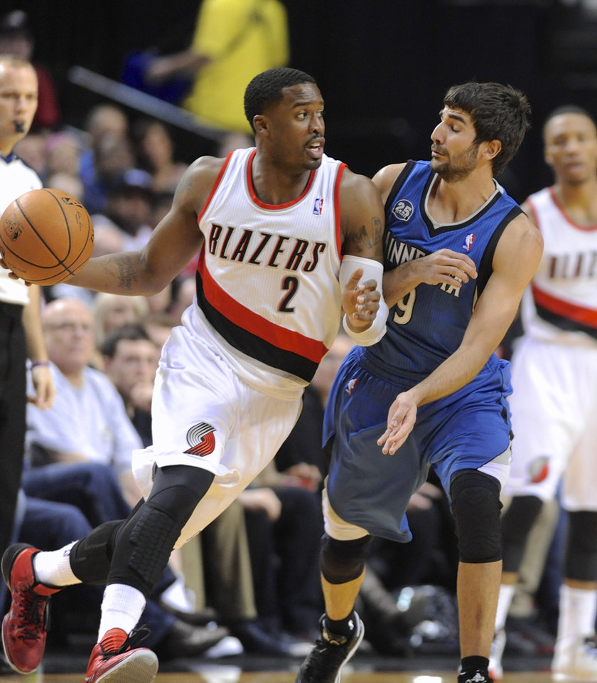 Photo - Minnesota Timberwolves'  Ricky Rubio (9) defends against Portland Trail Blazers' Wesley Matthews (2) during the first half of an NBA basketball game in Portland, Ore., Sunday, Feb. 23, 2014. (AP Photo/Greg Wahl-Stephens)