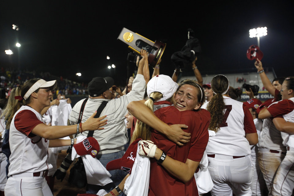 Kayla Braud (1) hugs graduate assistant Whitney Larsen after beating OU in the Women's College World Series softball championship at ASA Hall of Fame Stadium in Oklahoma City, Thursday, June 7, 2012.  Photo by Garett Fisbeck, The Oklahoman