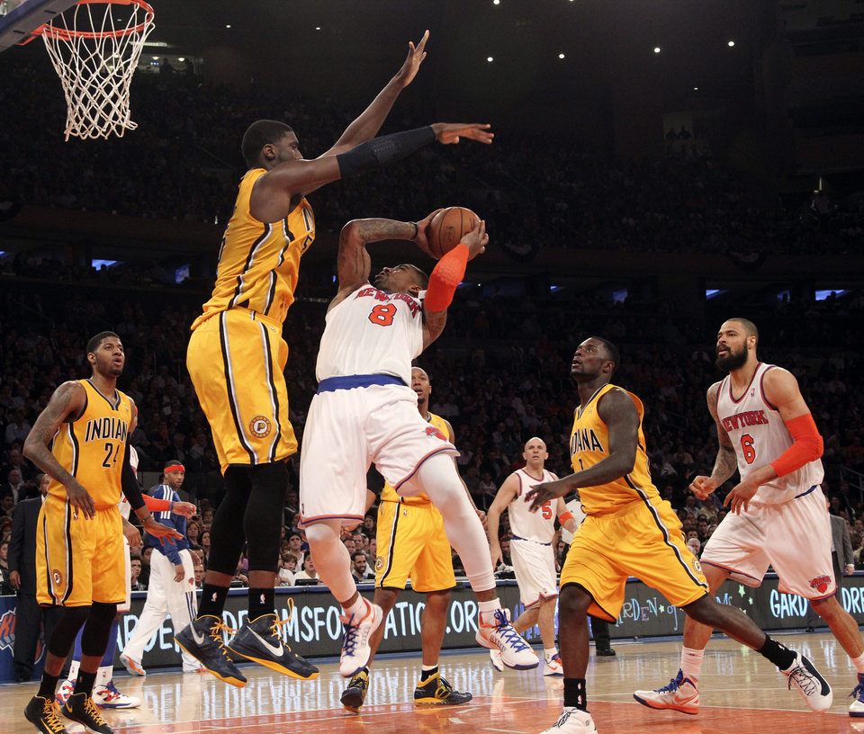 Photo - Indiana Pacers' Roy Hibbert, second from left, blocks New York Knicks' J.R. Smith from going to the basket in the second half of Game 2 of their NBA basketball playoff series in the Eastern Conference semifinals at Madison Square Garden in New York, Tuesday, May 7, 2013. The Knicks won 105-79. (AP Photo/Mary Altaffer)